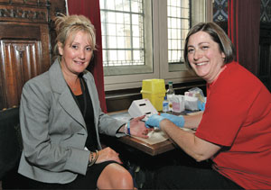 Caroline Dineage MP (left) having her cholesterol tested at the event