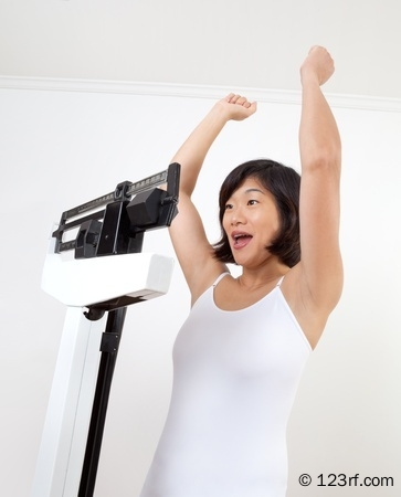 10413042-cute-mature-woman-on-a-weight-scale-cheering-happily-at-reaching-her-target-weight-white-background-